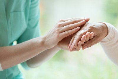 Caregiver holding residents hand
