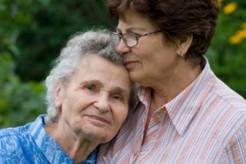 Woman caregiving for elderly parent.