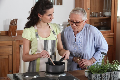 Chef preparing meal with elderly woman