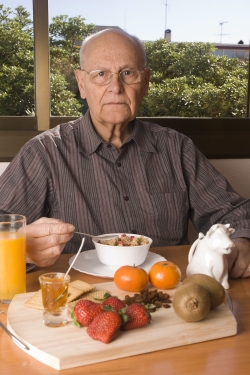 Elderly man eating healthy breakfast.