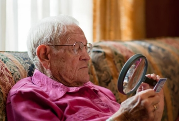 elderly man with magnifier