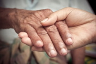 Hospice caregiver holding hand of elderly woman.
