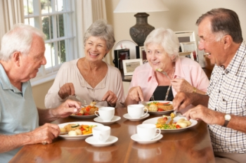 Senior couples eating together at retirement community.