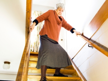 Senior woman walking down stairs.